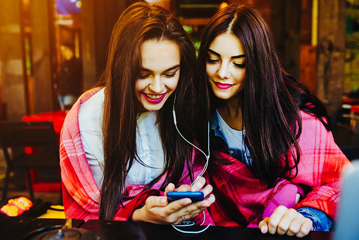 Two young and beautiful girl sitting at the table listening to music with a smartphone